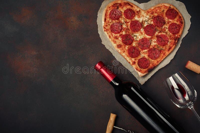 Serce kształtująca pizza z mozzarellą, sausagered z butelką wino i wineglas na ośniedziałym tle obrazy stock