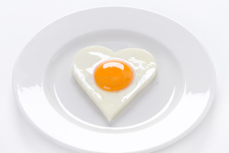Serce kształtujący jajko na talerzu zdjęcie stock