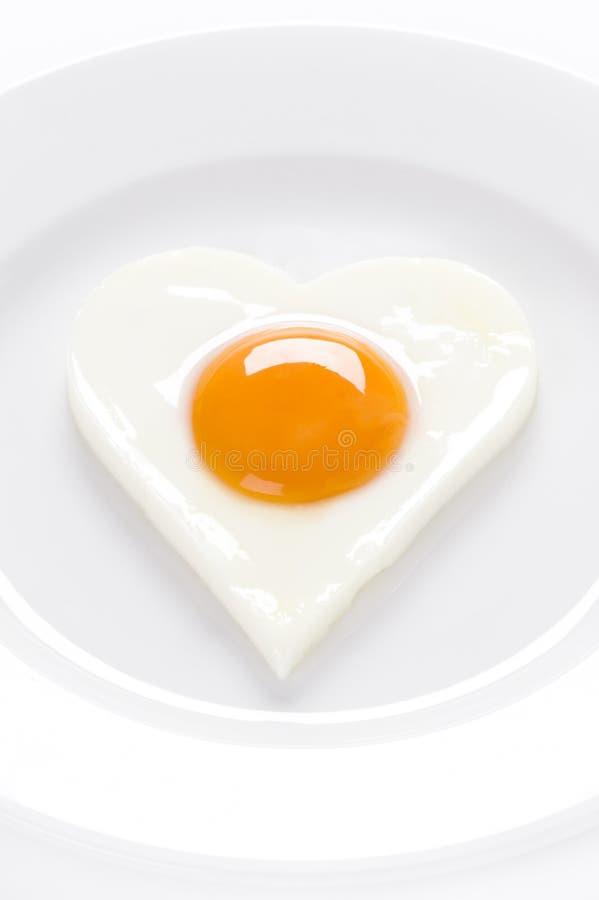 Serce kształtujący jajko na talerzu obrazy stock