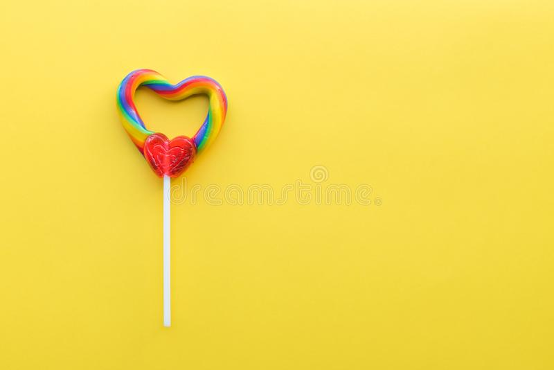 Serce kształtujący tęcza zawijasa lizak na jaskrawym żółtym stałym tle zdjęcia stock