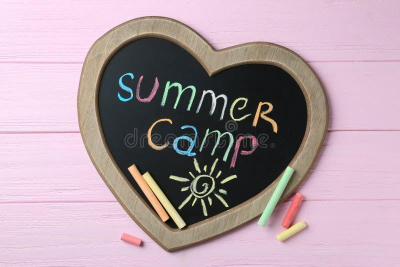 Serce kszta?tuj?cy blackboard z obozem letnim, rysunkiem i kred? teksta, wtyka na drewnianym tle ilustracja wektor