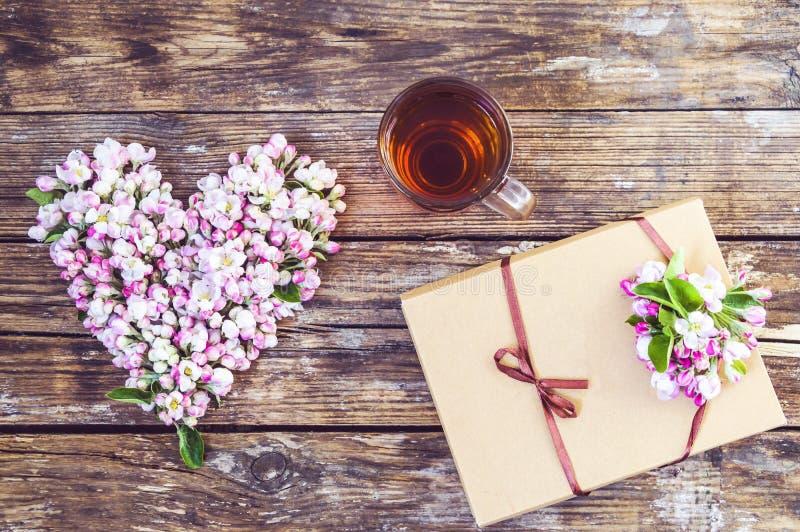 Serce kwiaty i p?czki jab?o?, fili?anka herbata, pude?ko z prezentem, cukierki w pude?ku Na starym drewnianym tle fotografia stock