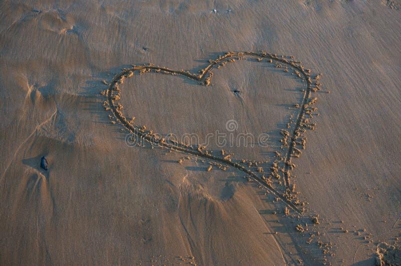 Serce na piaskowatej plaży obrazy royalty free
