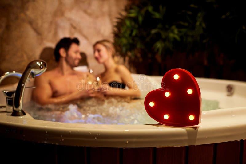 Serce na tle romantyczna para z szampanem w obraz royalty free