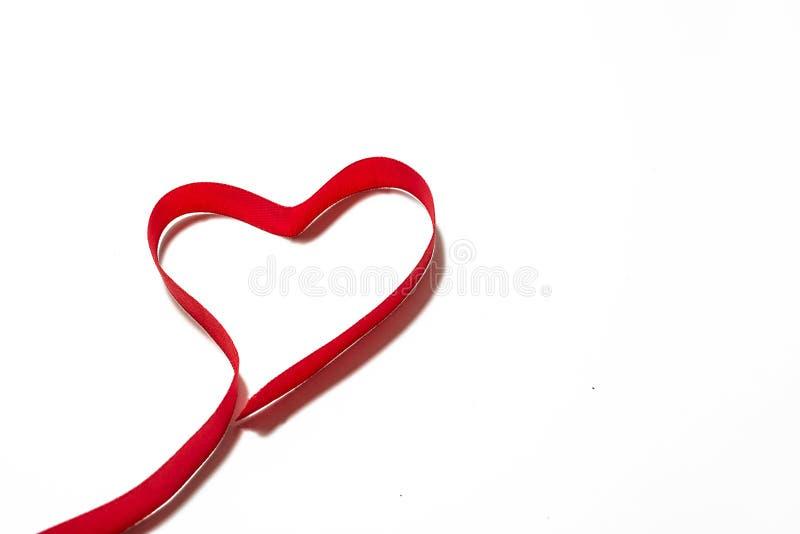 Serce robić czerwony faborek Umieszczający na białej księgi tle obrazy stock