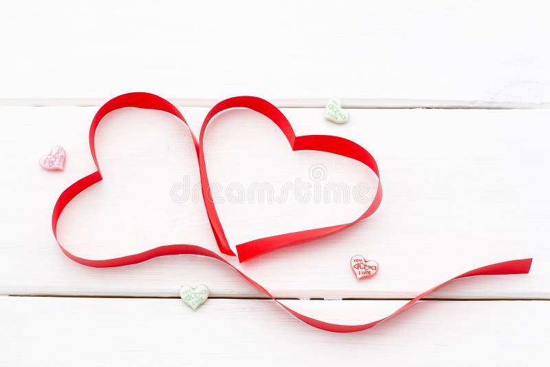 Serce robić czerwony faborek na białym drewnianym tle i few mali serca obrazy stock