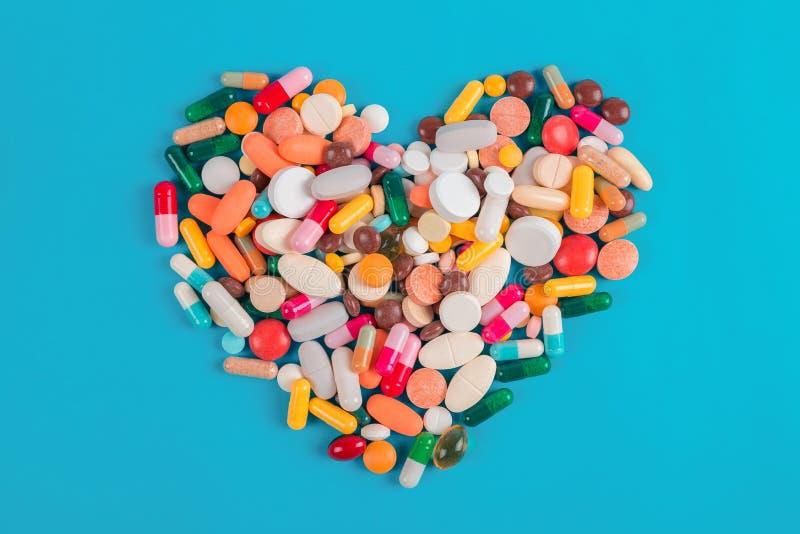 Serce robić kolorowe pigułki na błękitnym tle, Kierowej choroby lekarstwa obraz stock