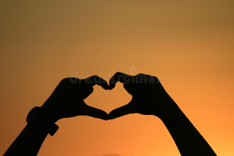 Serce robić wręcza tworzyć kierowego kształt z złocistą zmierzch sylwetką, cień kobieta ręki miłość podpisuje wewnątrz szczęśliwe obrazy stock