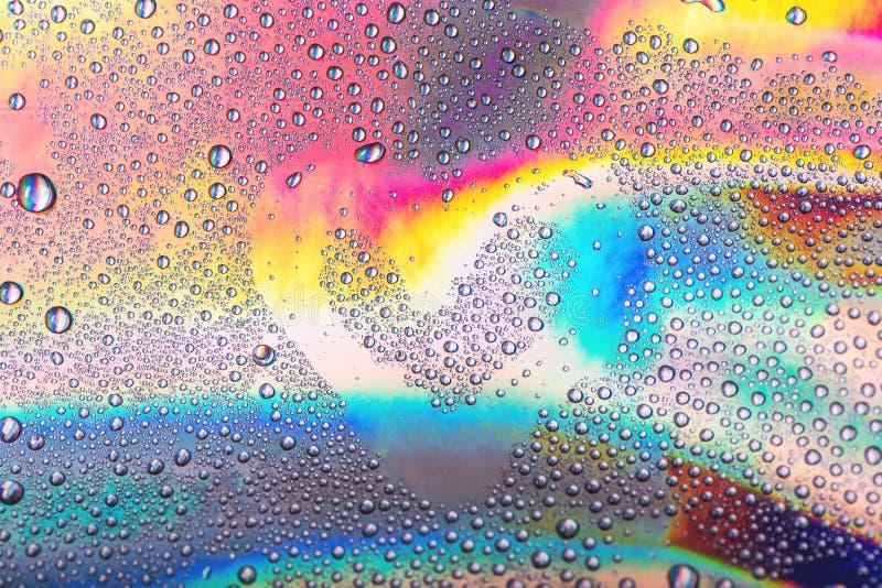 Serce rysujący na kroplach woda na wibrującym holograficznym neonowym tle zdjęcie royalty free