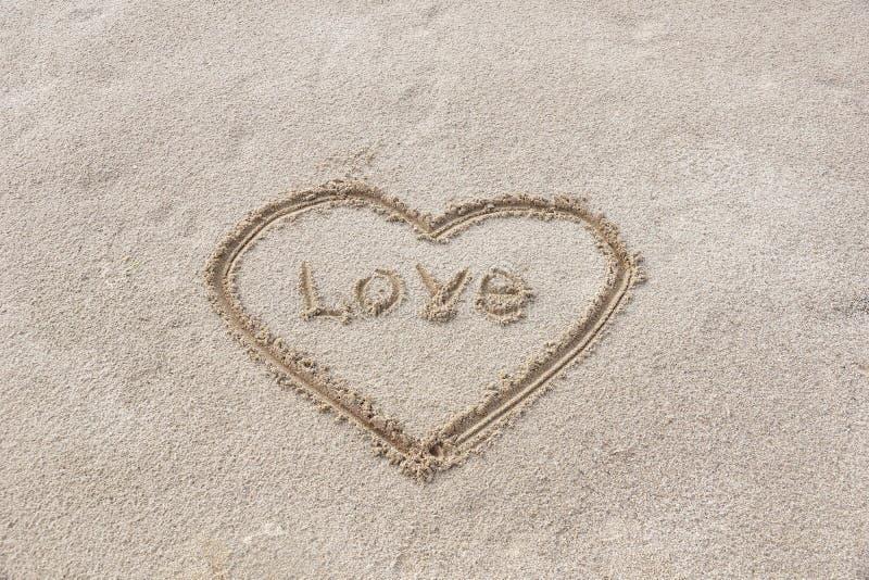 serce rysujący na piasku na plażowym kiju w centrum inscrip zdjęcia stock