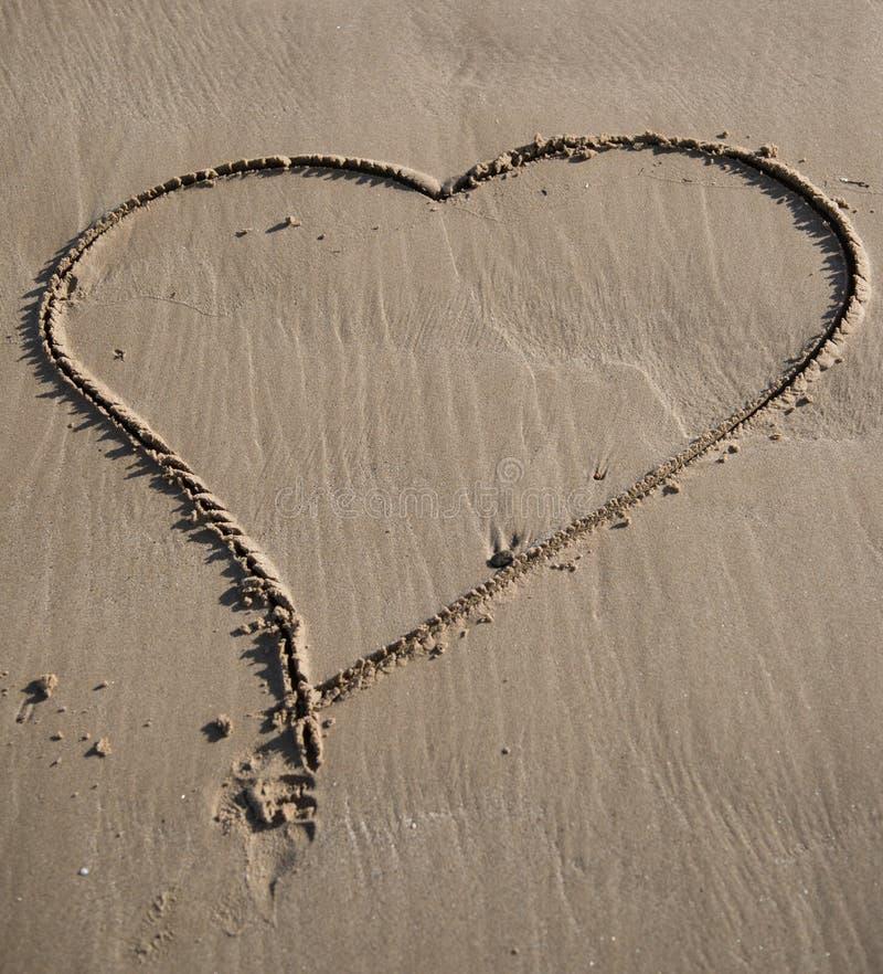 Serce rysuj?cy na piasku denna pla?a zdjęcie stock