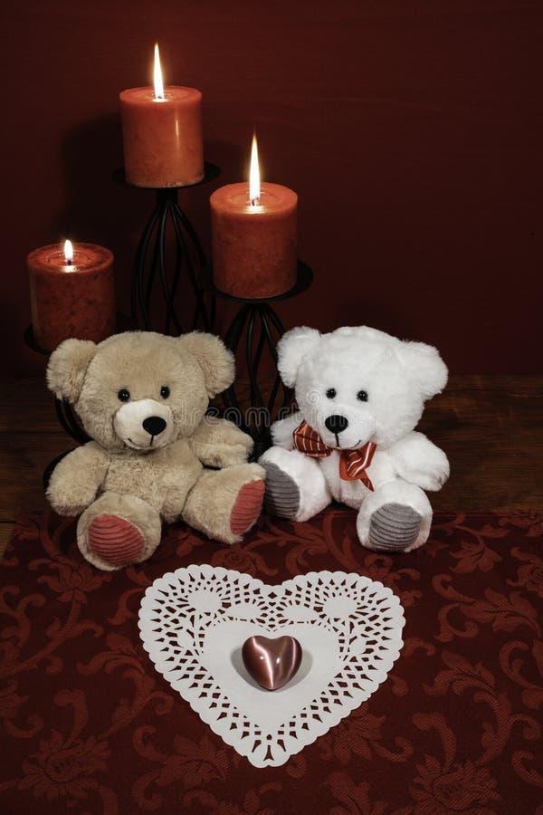 Serce shapped dollie, gemstone, trzy czerwonej świeczki w metali holoders i czerwieni róża, dwa misia na drewnianym stole fotografia royalty free