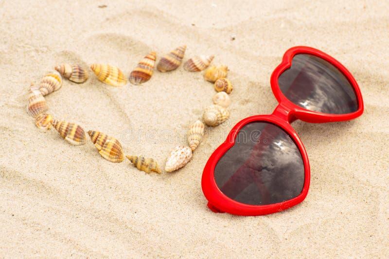Download Serce Skorupy I Okulary Przeciwsłoneczni Na Piasku Przy Plażą Zdjęcie Stock - Obraz złożonej z foremność, sunshine: 57655458