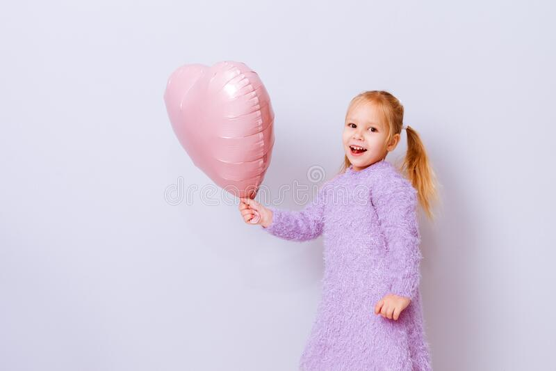 Serce szczęśliwych walentynek Dziewczyna uśmiechnięta różowym balonikiem na jasnofioletowym tle fotografia stock