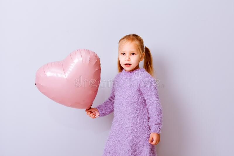 Serce szczęśliwych walentynek Dziewczyna uśmiechnięta różowym balonikiem na jasnofioletowym tle zdjęcia stock