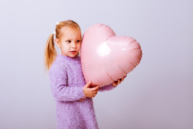 Serce szczęśliwych walentynek Dziewczynka naciska na swoje rączkowe serce na jasnofioletowym tle fotografia stock