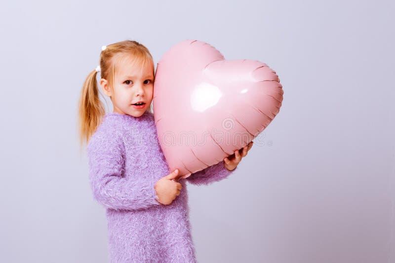 Serce szczęśliwych walentynek Dziewczynka naciska na swoje rączkowe serce na jasnofioletowym tle zdjęcie stock