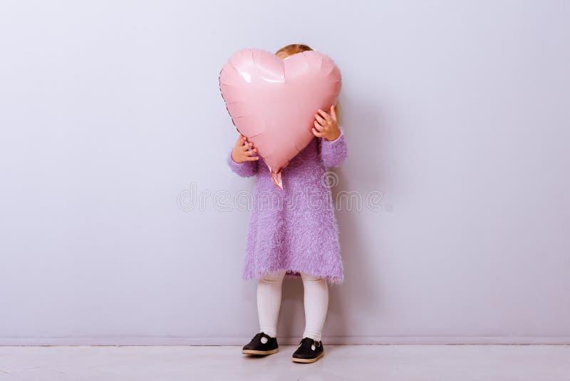 Serce szczęśliwych walentynek Dziewczynka pokryła twarz różowym balonem na jasnofioletowym tle obraz stock