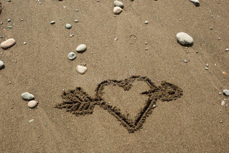 Serce w piasku z strzała zdjęcia stock