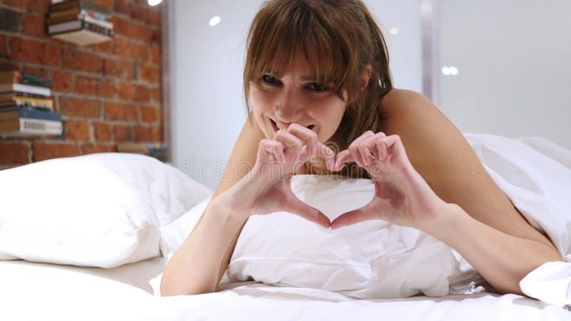 Serce znak młodej kobiety lying on the beach w łóżku na żołądku zdjęcia stock