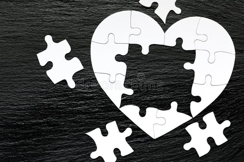 Sercowata wyrzynarki łamigłówka na koloru tle ?amig??wki serce na drewnianym tle Brakujący kawałek kierowa łamigłówka Serce zdjęcie stock