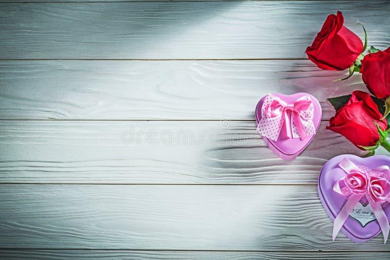 Sercowate metalu prezenta pudełek czerwone róże na drewnianej deski wakacjach zdjęcia stock