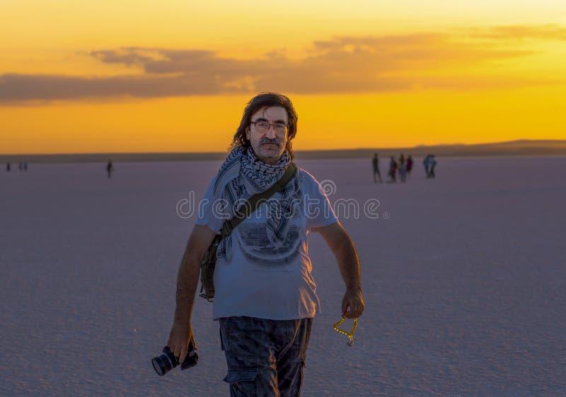 Sereflikochisar/Turquia - 7 de julho de 2019: Uma silhueta de um homem turco guarda uma câmera em uma mão e grânulos na outra mão fotografia de stock