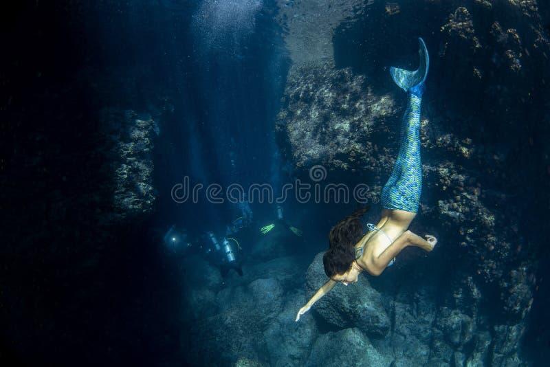 Sereia que nada debaixo d'?gua no mar azul profundo imagem de stock