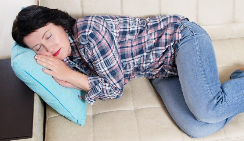 Serene Beautiful Middle Aged Woman, das auf der Couch Nickerchen macht Schlafen nach Tag der harten Arbeit stockfotos