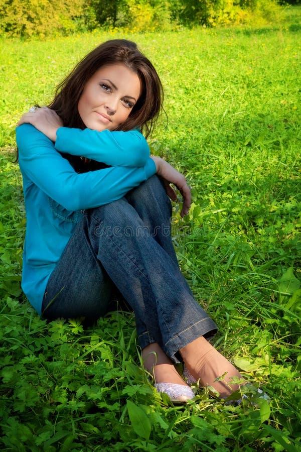 Serene beautiful woman resting on green grass stock photo