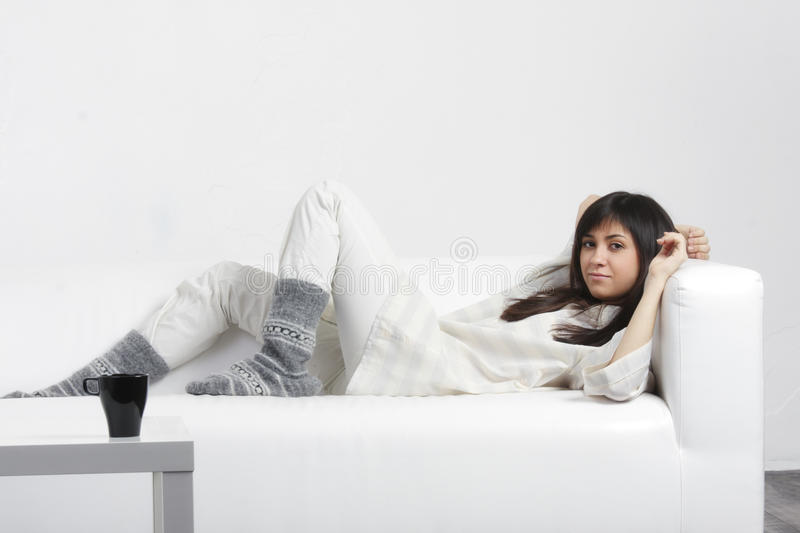 Serene brunette laying down on sofa royalty free stock image
