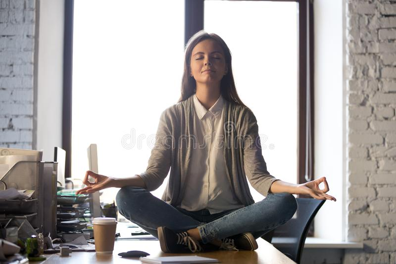 Serene calm business woman sit on office desk meditating. Serene calm business woman sit on office desk taking break for meditation, mindful employee doing yoga royalty free stock image