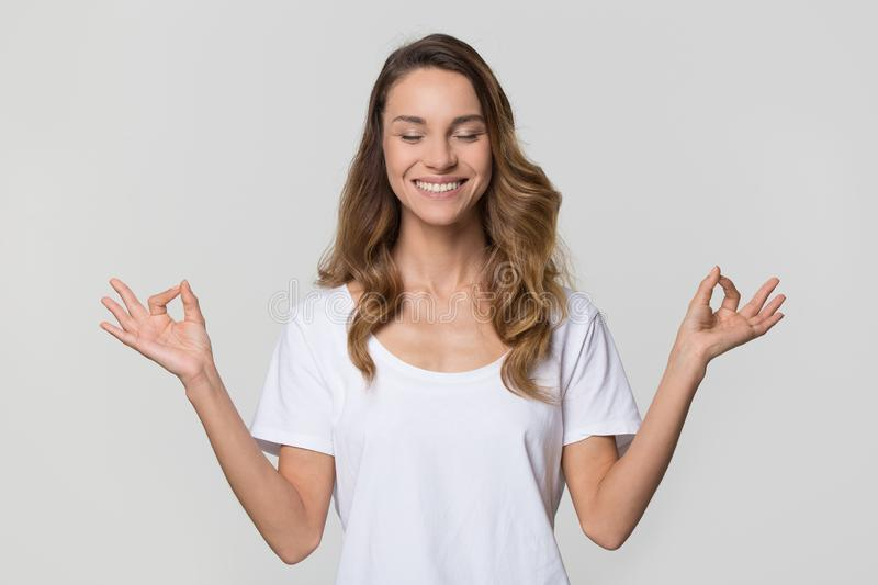 Serene calm woman doing yoga exercises on white blank background. Serene calm woman smiling doing yoga exercises relaxing on white blank studio wall, happy young stock photo