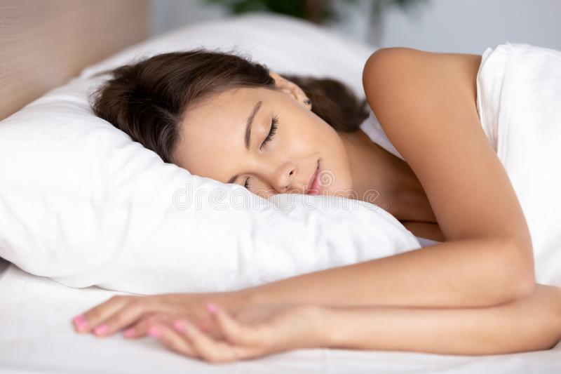 Serene calm young woman sleeping well on orthopedic soft pillow. Under warm duvet in comfortable cozy fresh bed having good night peaceful healthy sleep royalty free stock photography