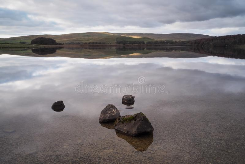 Serene water of Malham Tarn with the reflection of the afternoon sun on the hills, Yorkshire Dales, royalty free stock image