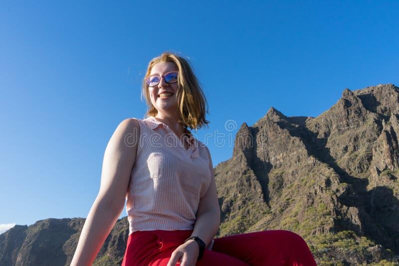 Serene Cute Tourist Frau, lachen und bewundern die Freiheit und die Landschaft im Berg, sitzen in einem Felsen Modellsitz und lizenzfreies stockbild