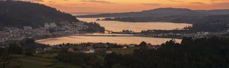 Serene dusk panorama della città medievale di Pontedeume con il suo ponte di ferro e di pietra Oro cielo La Coruña Galicia immagine stock