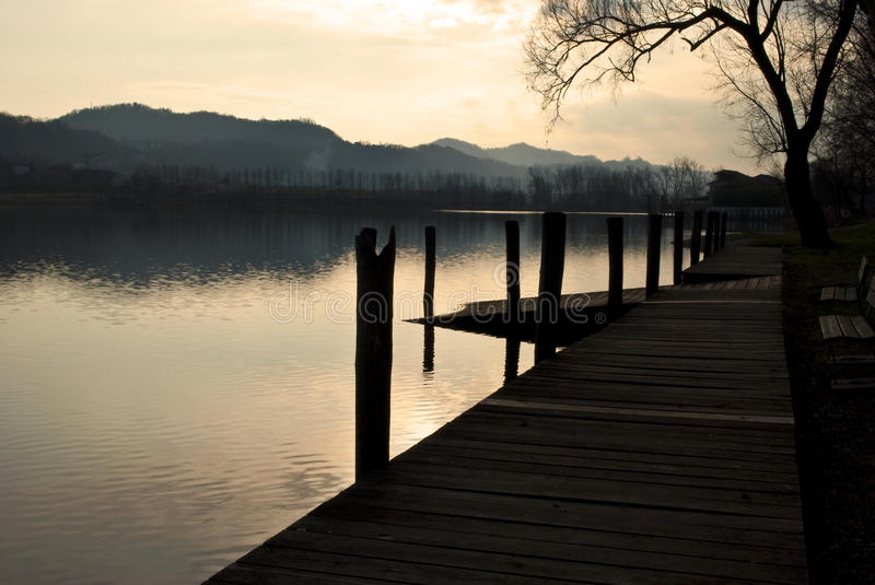 Serene evening at lake. A serene place by the lake with two benches and the wharf royalty free stock photo