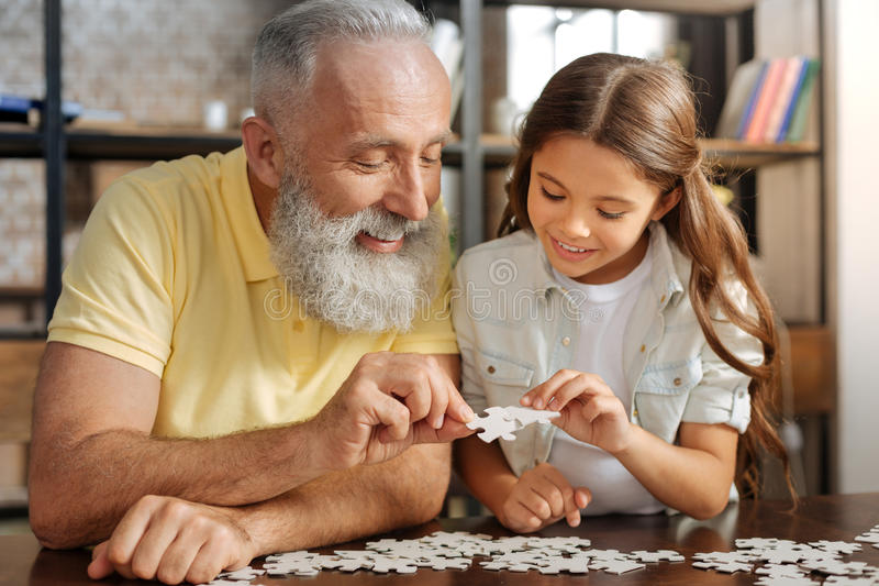Grandfather and granddaughter connecting two jigsaw puzzle pieces. Serene family. Cute pre-teen girl sitting at the table next to her grandfather and assembling royalty free stock photography