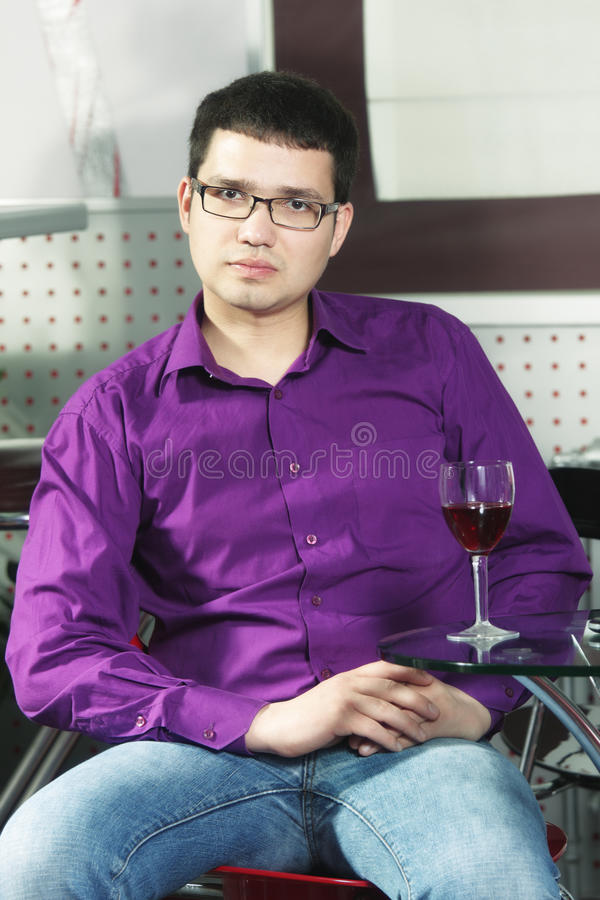 Serene guy in cafe with glass of wine
