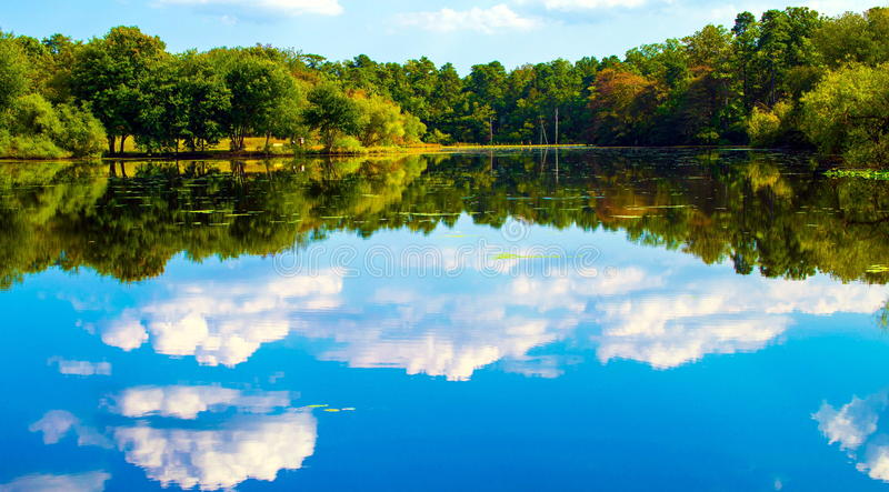 Serene Lake. A very sunny day at a local lake. Reflections were really good that day. This lake resides in a county park in NJ. Colors were very vibrant that day stock image