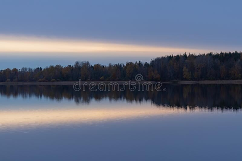 Serene landscape. Sunset on the lake, calm water surface, symmetrical reflection royalty free stock photography