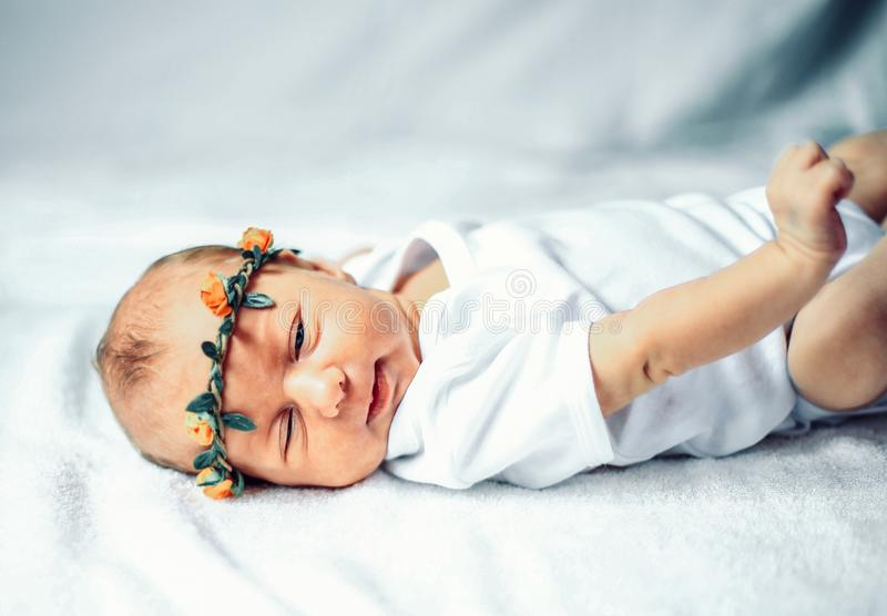 Serene newborn baby in the wreath lying on the white sheet. The photo has a empty space for your text royalty free stock image