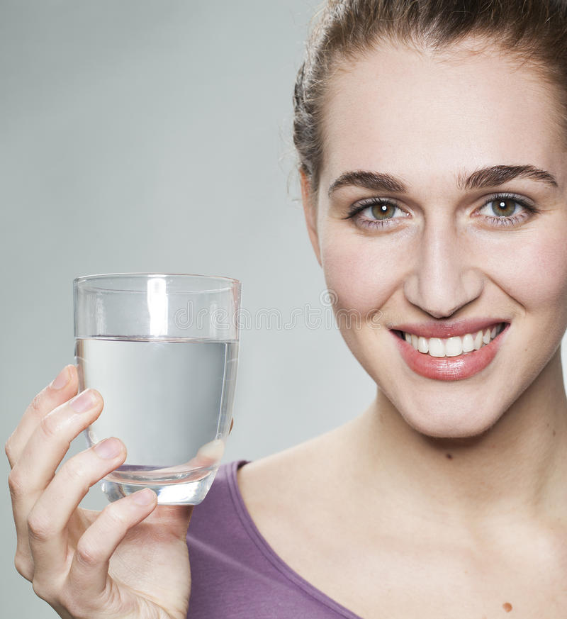 Serene 20s girl showing glass of fresh tap or mineral water. Smiling young beautiful woman wearing purple shirt displaying glass of pure tap water royalty free stock photo