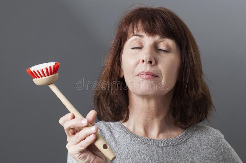 Serene 50s woman concentrating for cleaning dishes stock photography