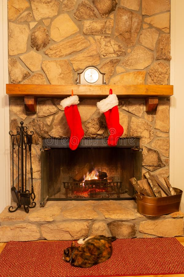 A stone fireplace with two Christmas stockings hung on the mantle and the family cat relaxing by the fire. royalty free stock photography