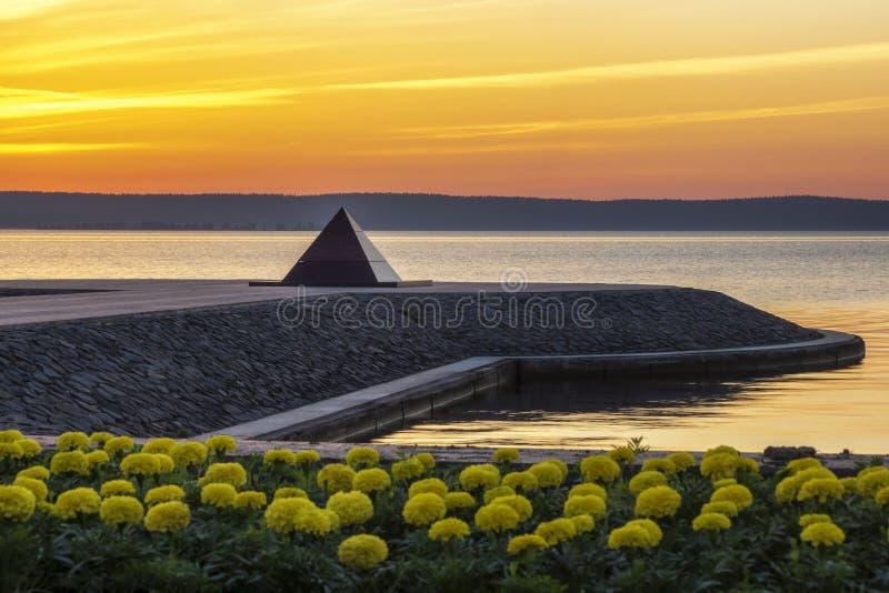 Serene sunrise on city embankment of lake royalty free stock image