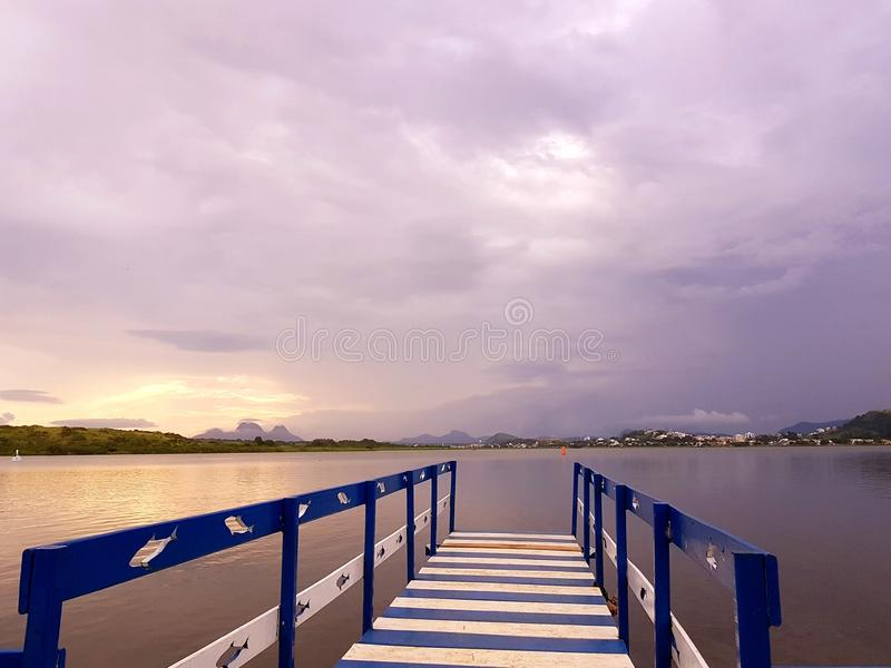Serene sunset in Imboassica Lagoon Macaé - Brazil. Deck and sunset with violet clouds in sky at lagoon Imboassica in the Macaé City- Brazil stock photography
