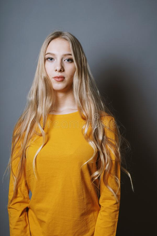 Serene teenage girl with very long blond hair stock photo