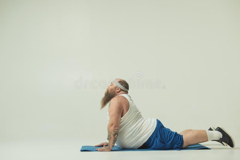 Serene thick guy doing yoga on sports carpet royalty free stock image